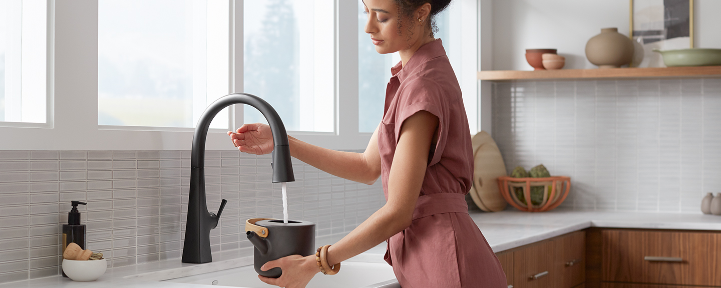 Woman using touchless faucet